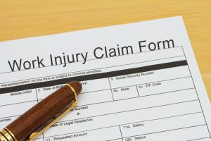 Filing a Work Injury Claim Form, Work Injury Claim Form with a pen on a desk futterweit law services